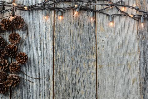 christmas lights and pinecones on rustic wood background