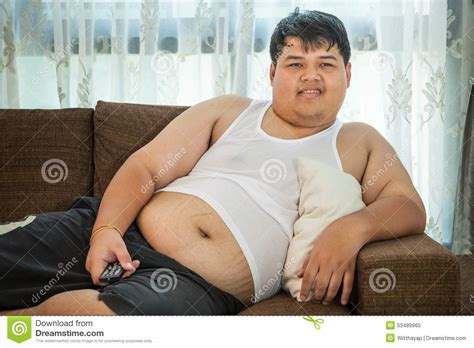 lazy guy on couch overweight guy sitting on the couch to watch some tv stock