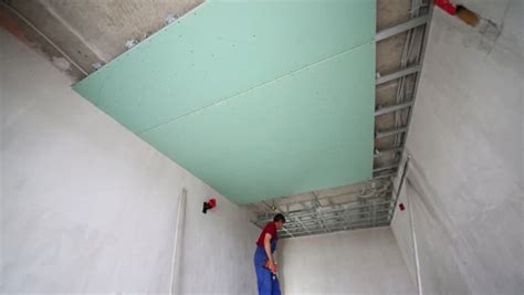 Laser Level For Drop Ceiling by Two Workers With Screwdriver And Building Level Measure