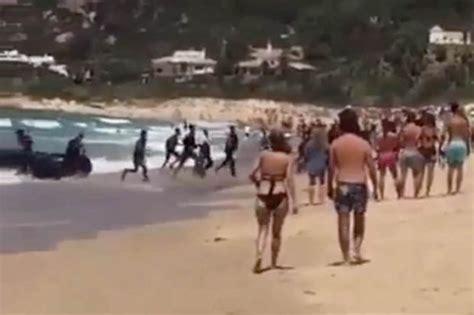 refugee boat lands on tourist filled spanish beach in - Refugee Boat Landing In Spain