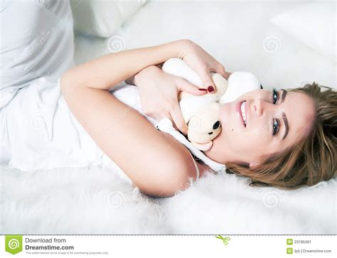 girls laying in bed beautiful girl laying in white bed with bruin stock image
