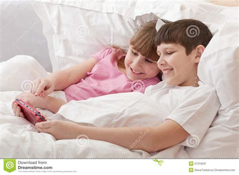 games to play in bed children in bed playing game console close up stock