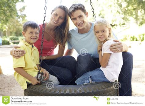 family swing family sitting on tyre swing in playground stock photo