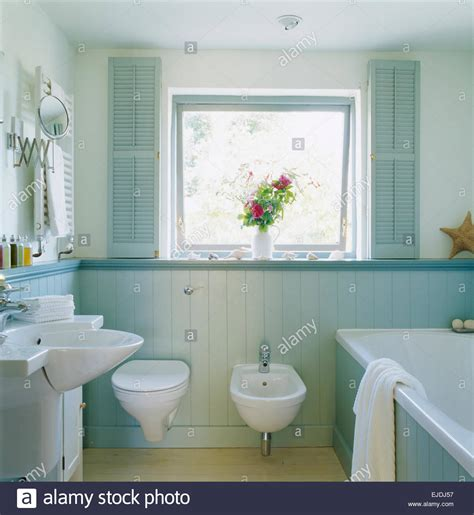 painted tongue and groove bathroom pale blue shutters on window above toilet and bidet in