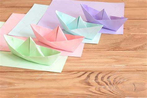 Origami Color - cuatro color origami juguetes de barcos sobre una mesa de