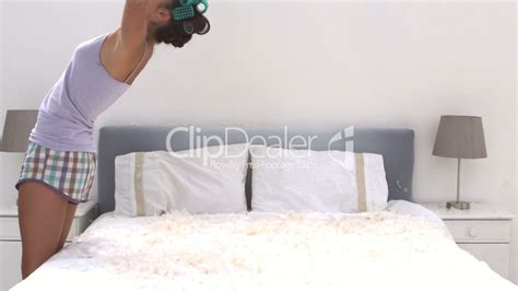 bed full of pillows cute woman bouncing on her bed full of pillow feathers
