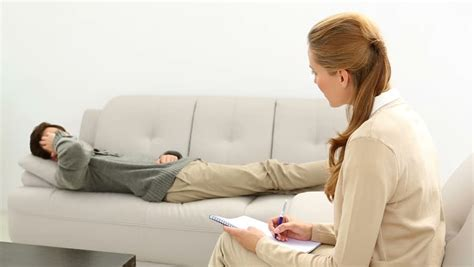 couch counseling man comforting his upset partner at therapy session stock