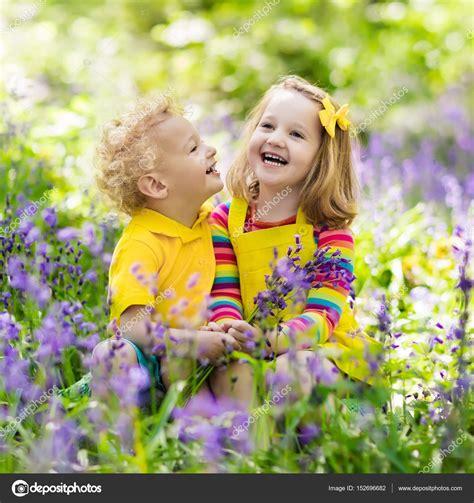 bambini con fiori bambini giocano in giardino di fioritura con fiori di