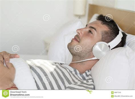 lay on the bed young man laying in bed listening music stock photo