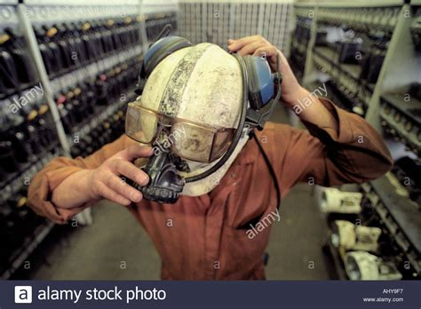 miner hard hat with attached light a miner puts on his hard hat and light in the l room of