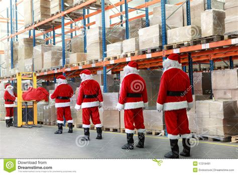 santas warehouse santa clauses in the line for gifts in warehouse stock