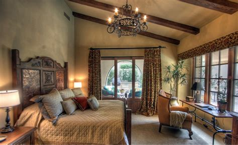 mediterranean inspired bedroom exposed wooden roof beams in bedroom