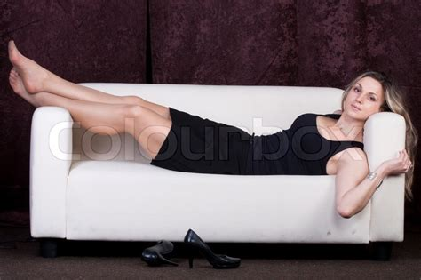 girl on a sofa girl in a black dress lie on a sofa high heel shoes stand