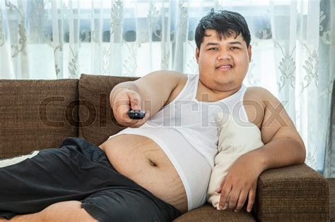 the couch guy overweight asian guy sitting on the couch with remote in