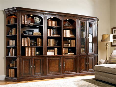 Light brown wooden bookcase with three shelves plus double glass doors placed on the white floor
