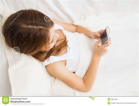 girls in bed little girl lying in bed with smartphone at home stock