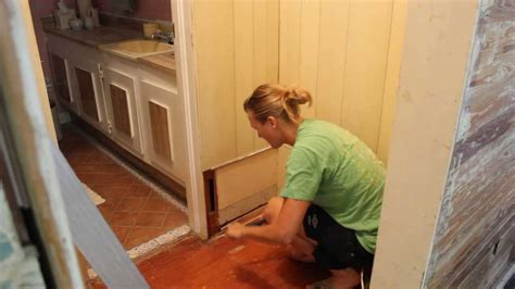 Removing Wainscoting by Using A Pry Bar To Remove Paneling And Nails