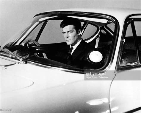 roger moore  simon templar   promotional portrait   wheel   volvo p sports car