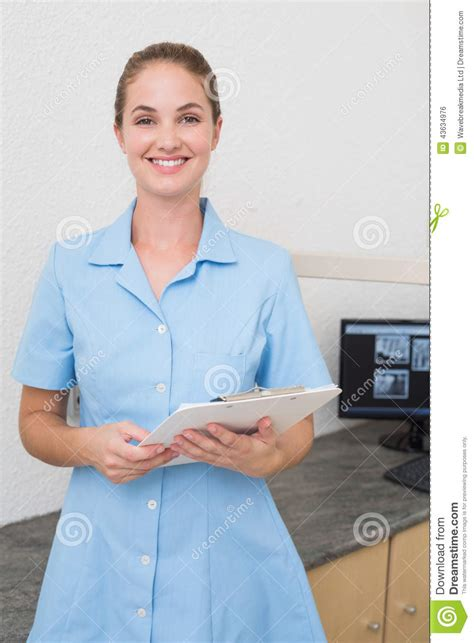 smiling dental assistant looking at holding