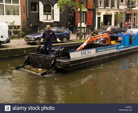 trash boat amsterdam man works with retrieving pole on canal cleaning barge