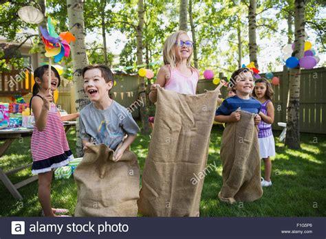 backyard cing birthday party kids enjoying sack race at backyard birthday party stock