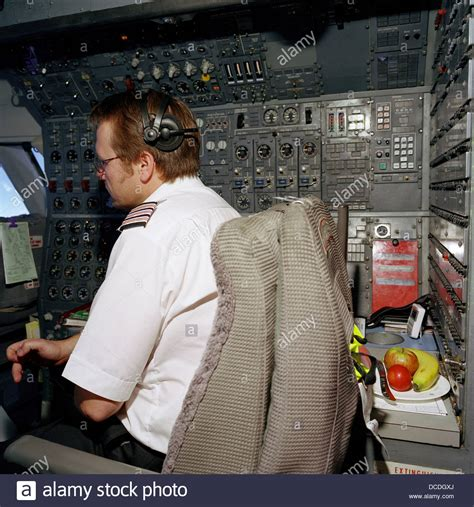 an airline flight engineer occupies his own seat in the cockpit of a stock photo royalty free
