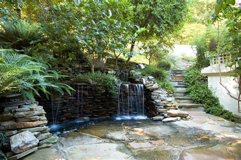 backyard rock wall modern landscaping ideas with waterfalls on a stone wall