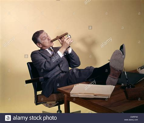 cigarette smoke extractor fans 1960s successful businessman sitting with shoes propped on