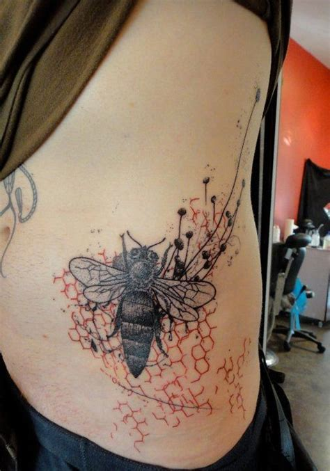 black bee and red honeycomb tattoo on ribs by xoil