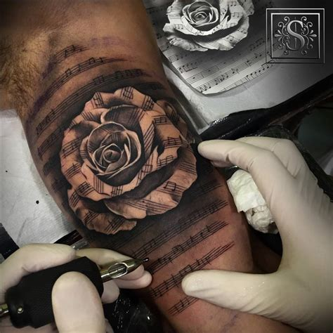 rose and music tattoo black and grey style staff artist