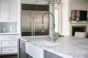charcoal grey island with farmhouse sink and pull out faucet transitional kitchen