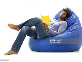 Surprising young man in bean bag chair reading book stock photo getty