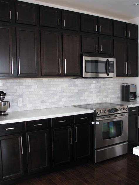 dark birch kitchen cabinets with shining white quartz counters and white marble backsplash