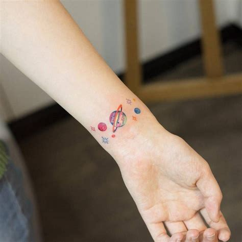 small inner wrist tattoos small planets on the left inner wrist artist