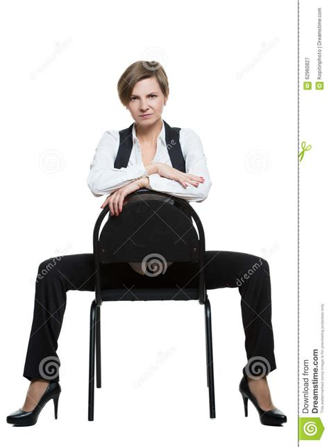 how to be a dominant woman in the bedroom woman sits astride a chair arms crossed dominant stock
