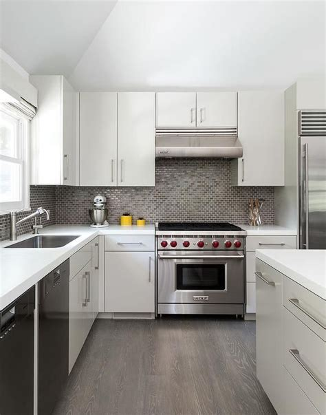 white and gray kitchen features white flat front cabinets