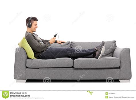 lying on a sofa young guy lying on sofa and listening to music stock photo
