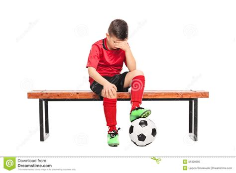 sad bench sad kid in soccer uniform sitting on a bench stock photo