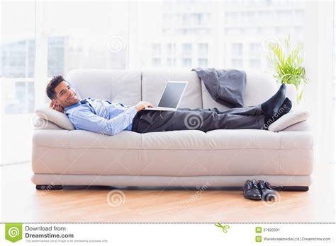 lying on a sofa businessman lying on sofa using his laptop smiling at