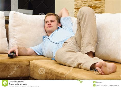 lying on a sofa man lying on sofa watching tv stock photos image 20340293