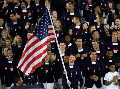 Michael phelps carries the american flag as he leads team usa into rio
