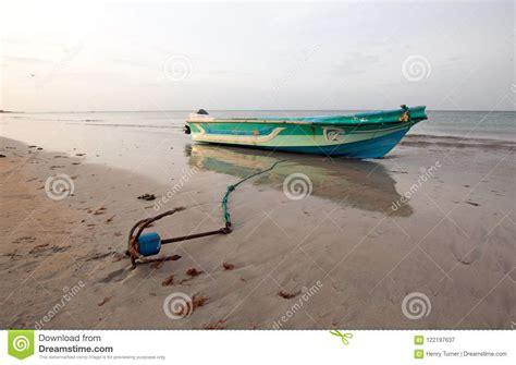 small fishing boat anchors small fishing boat with anchor at sunset on nilaveli beach