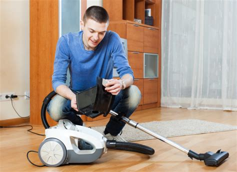 man vacuuming with vacuum cleaner on parquet floor in living room photo free download