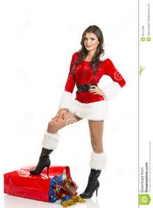 Smiling sexy girl dressed in santa claus clothes posing with one leg