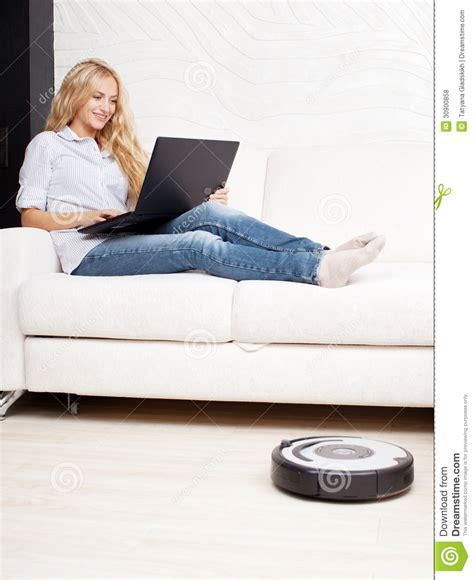 lie on the couch woman lying on the sofa and the robot vacuum cleaner
