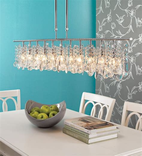 Hanging Low Modern Crystal Linear Chandelier Above Solid Wooden Dining Table Painted With White