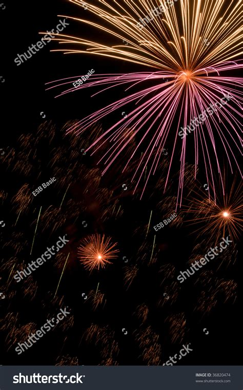 whitish pink pink and whitish burst of fireworks above smaller bursts