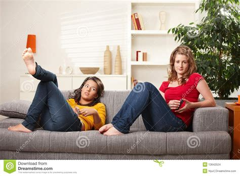 girls having on a couch teen girls relaxing on sofa stock images image 13642524