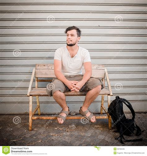 person sitting on a bench stylish man sitting on a bench royalty free stock photo