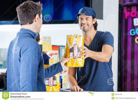 worker selling popcorn to man at concession stand stock